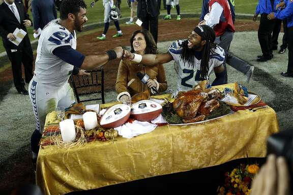Seattle Seahawks' Richard Sherman and Russell Wilson celebrate over turkey after 19-3 win over San Francisco 49ers in NFL game at Levi's Stadium in Santa Clara, Calif., on Thursday, November 27, 2014.