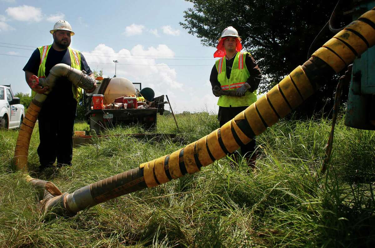 Workers Alfredo Torres and Adam Velasquez take soil samples along Texas 288 on July 8, 2016, near downtown Houston.