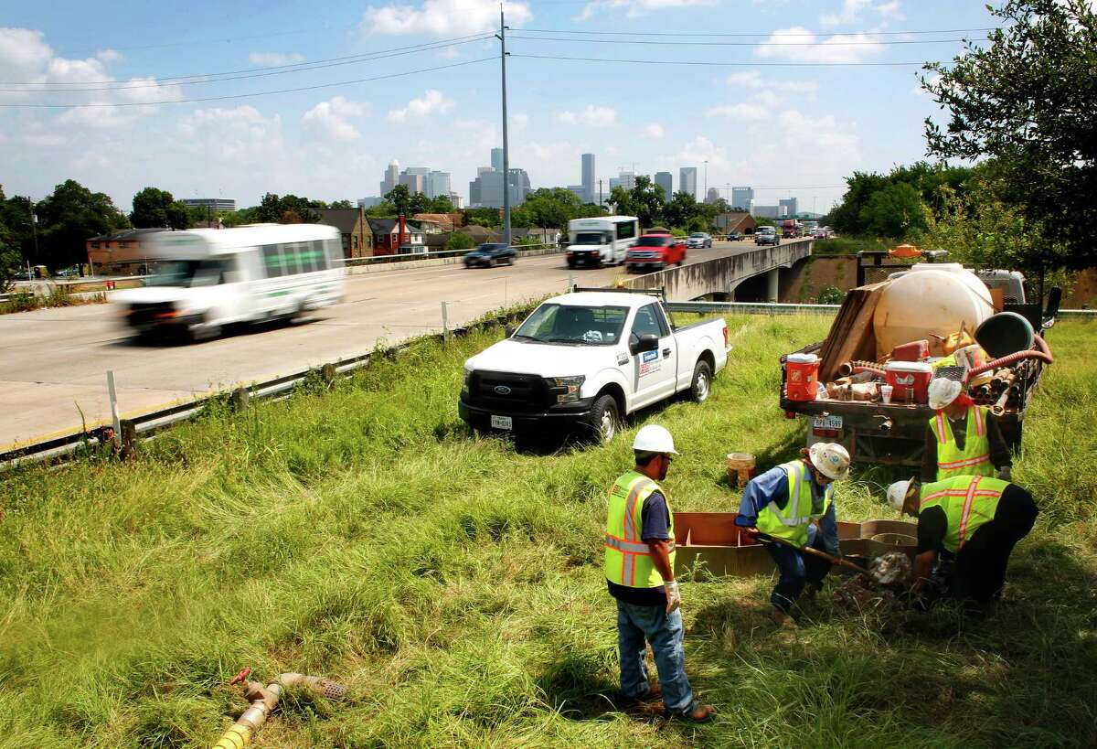 Workers take soil samples to be tested in preparation for future toll structures along Texas 288 on July 8.