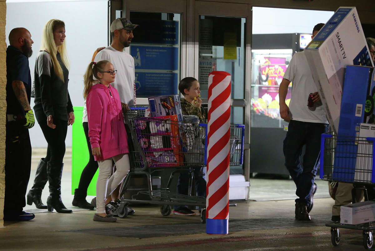 Customers at the Wal-Mart at Loop 1604 and U.S. Highway 281 North leave with merchandise on Gray Thursday November 24, 2016 on Thanksgiving day.