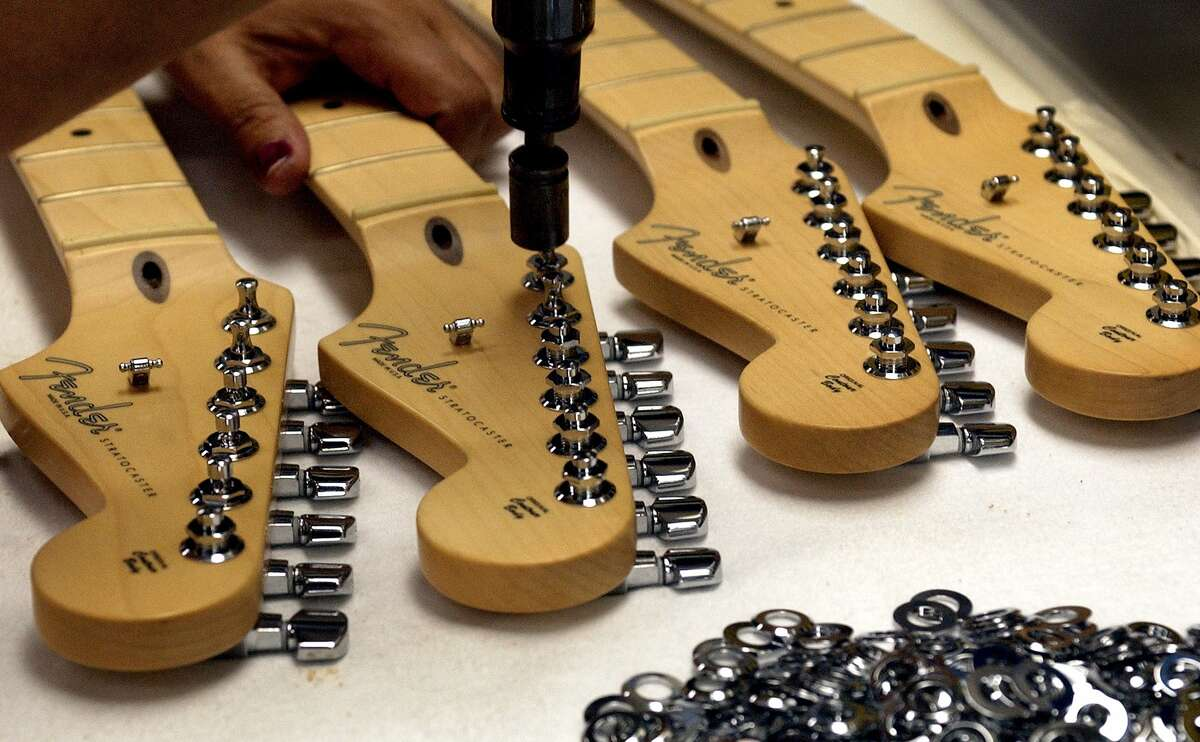 A worker attaches tuning heads to Fender Stratocaster head stocks at the Fender factory in Corona, Calif.