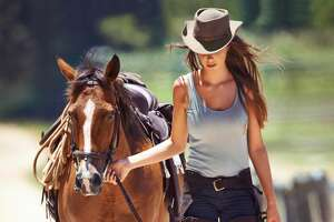 A gorgeous cowgirl leading her horse along a country lane