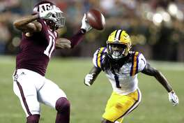 Texas A&M wide receiver Josh Reynolds (11) makes a one-handed catch against LSU defensive back Donte Jackson (1) during the second quarter of an NCAA football game at Kyle Field on Thursday, Nov. 24, 2016, in Houston.