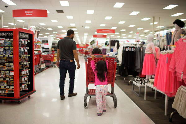 Isabela Bella, 3, pushes a shopping cart during Black Friday at Target, Friday, Nov. 25, 2016, in Houston.