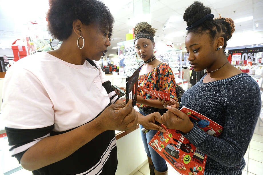 From left, Towona Washington and daughters Nikki and Shuntasia coordinate their scratch-off coupons as they make a bee-line to the jewelry counter for the sale special on diamond stud earrings at J. C. Penney Thursday. Although some retailers have scaled back on opening during the holiday and have opted back to Black Friday, several have stuck with their Thanksgiving hours. Photo taken Thursday, November 24, 2016 Kim Brent/The Enterprise Photo: Kim Brent / Beaumont Enterprise
