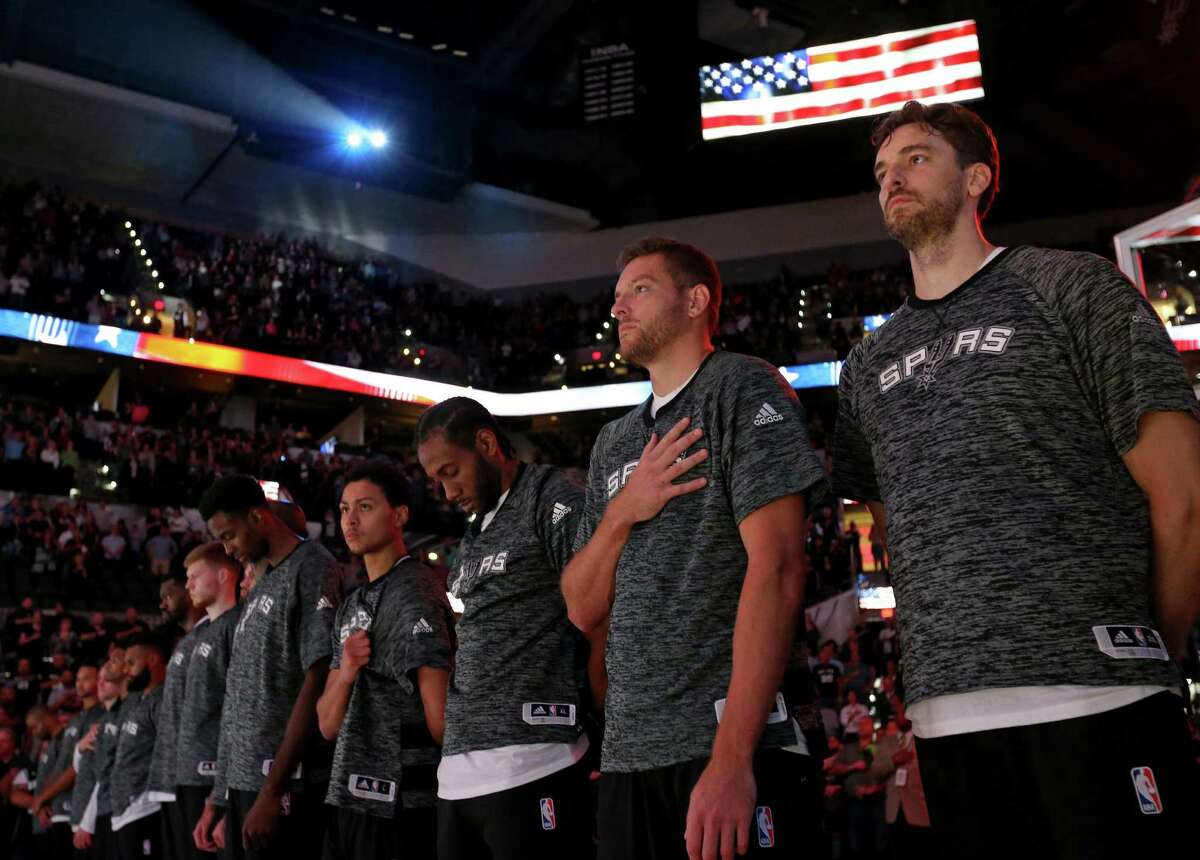 Spurs' Pau Gasol (from right), David Lee, Kawhi Leonard, Bryn Forbes, and others stand during the national anthem before their preseason game with the Houston Rockets on Oct. 21, 2016 at the AT&T Center.