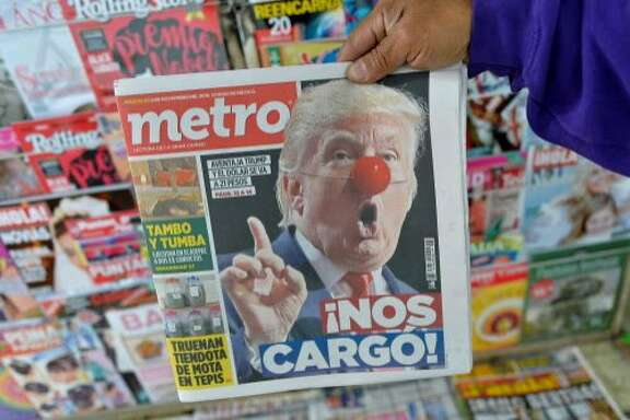 A Mexican holds a newspaper with headlines referring to the eventual triumph of Donald Trump on November 9, 2016 in Mexico City. / AFP PHOTO / PEDRO PARDOPEDRO PARDO/AFP/Getty Images