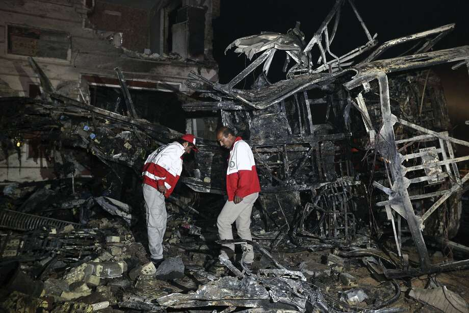 Iranian civil defense workers search for survivors of a car bombing near Hilla, south of Bagh dad. Islamic State claimed responsibility for the blast, which killed about 40 Iranian pilgrims. Photo: Hadi Mizban, Associated Press