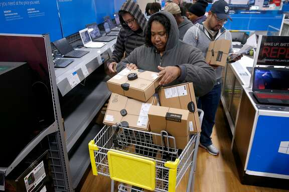 Kecia Jarvis is at the front of the pack of shoppers loading up on $99 laptops and other Black Friday deals at the Best Buy in Emeryville, Calif. on Friday, Nov. 25, 2016.