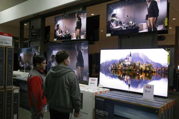 Black Friday shoppers pause to look at flatscreen televisions on sale at the Best Buy in Emeryville, Calif. on Friday, Nov. 25, 2016.