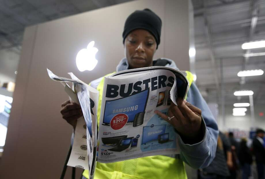 Markee Hill flips through an advertising insert while shopping for Black Friday deals at the Best Buy in Emeryville, Calif. on Friday, Nov. 25, 2016. Photo: Paul Chinn, The Chronicle