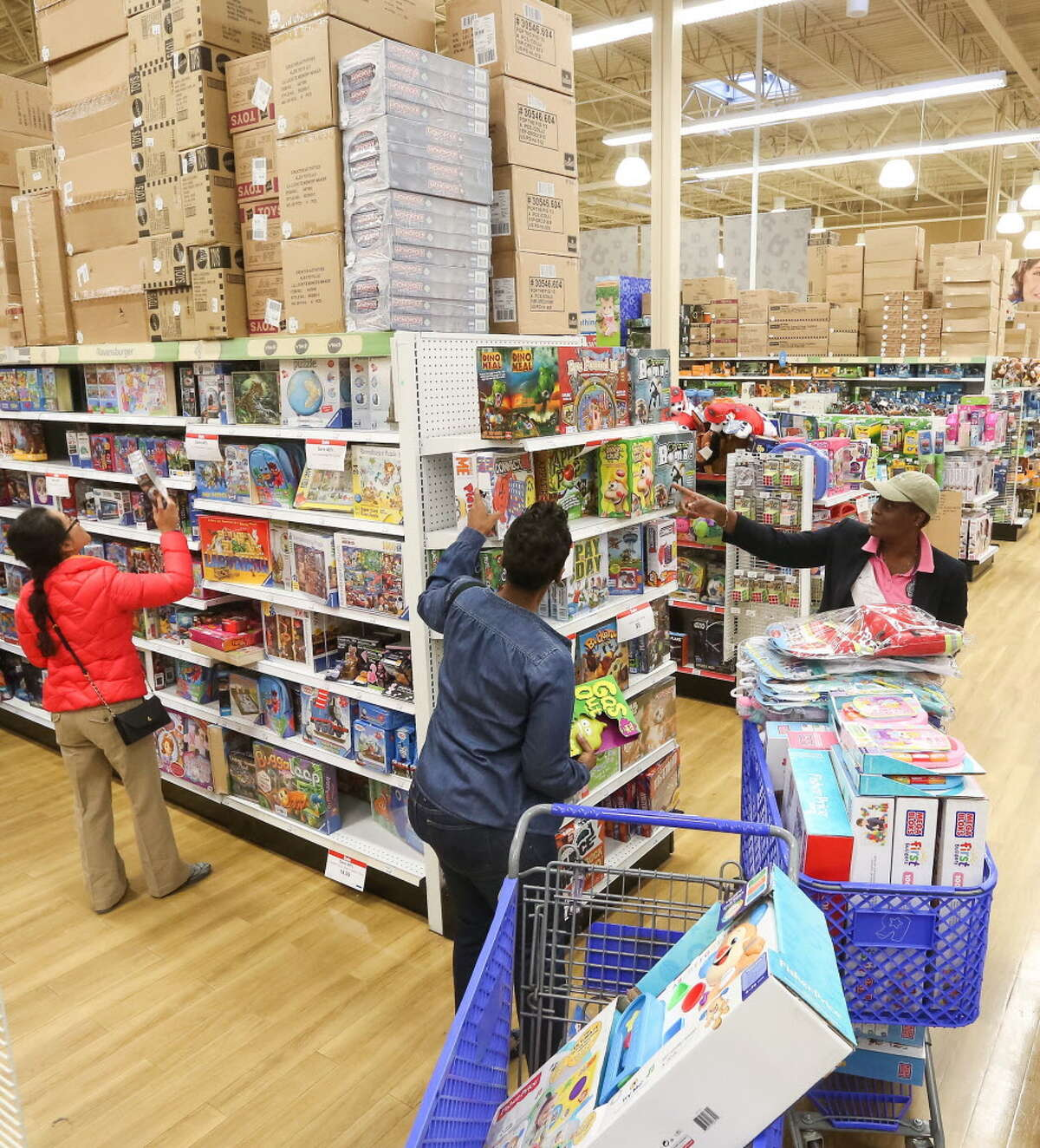 Theresa Sackey, right, and her step-sister Bridgette Laryea, center, shop for toys to send to Ghana, at a Toys R Us location on Black Friday, Friday, Nov. 25, 2016 in Houston. The pair were taking advantage of Black Friday sales to buy toys for children in Africa.
