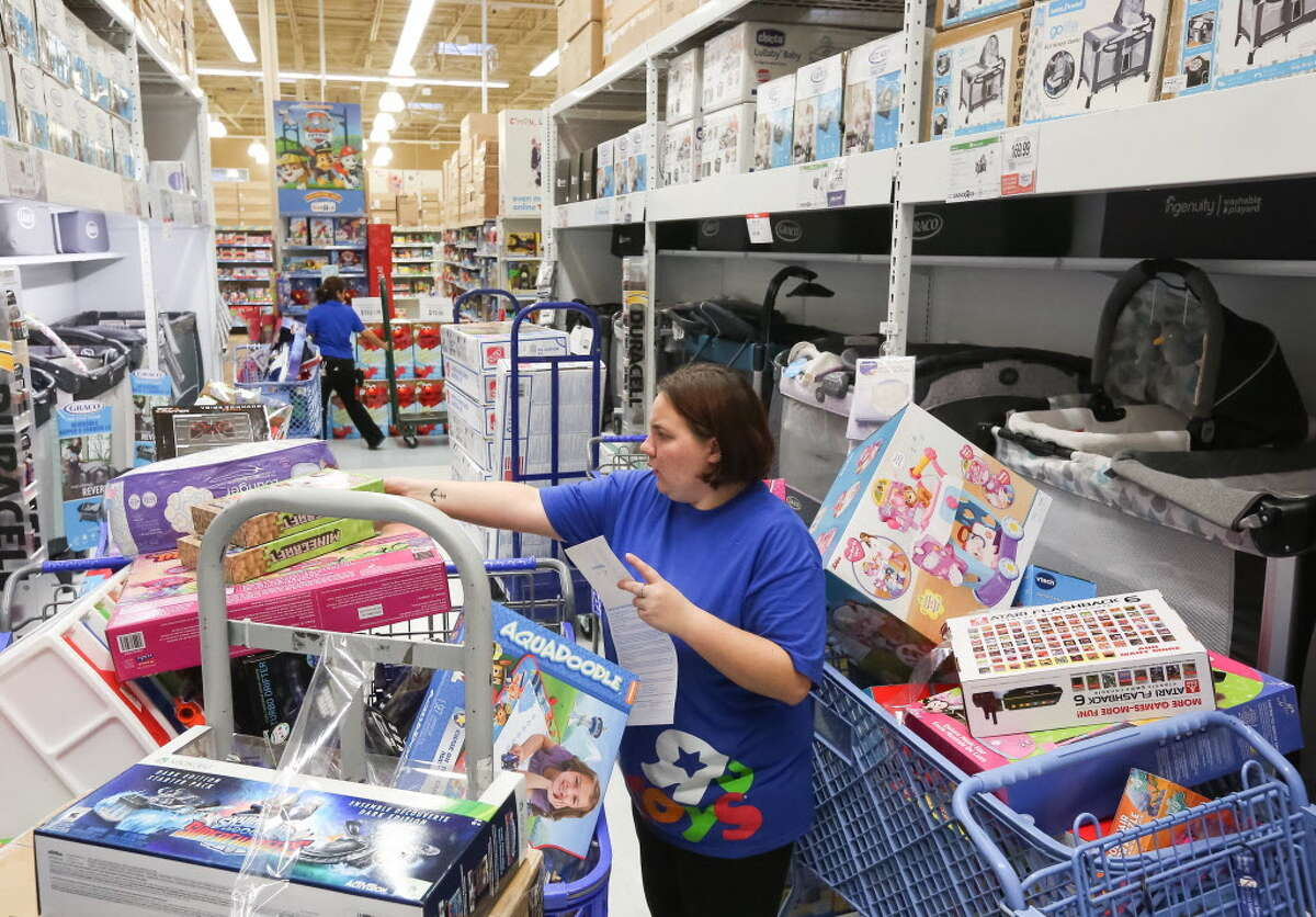 Mariah Smith works to fill online orders at a Toys R Us location on Black Friday, Friday, Nov. 25, 2016 in Houston.