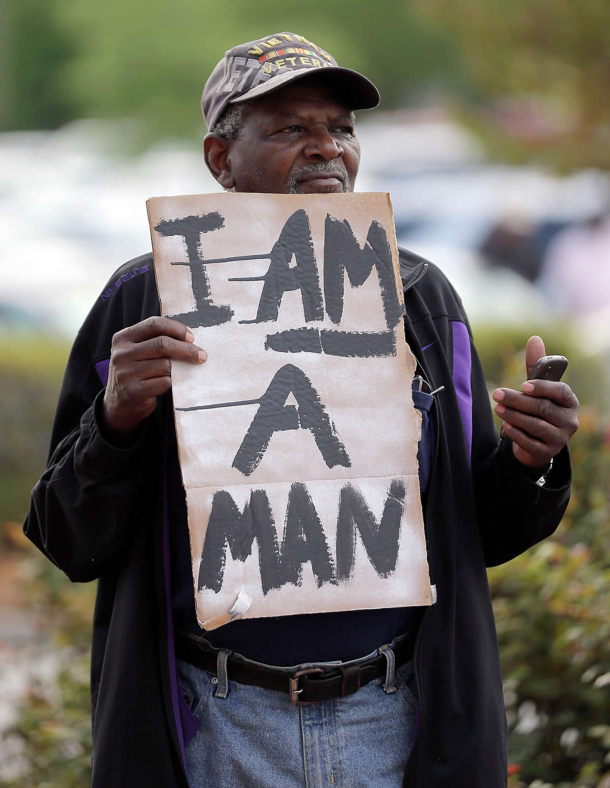 Robert Jackson holds a sign during a protest in shooting death of Walter Scott at city hall in North Charleston, S.C., Wednesday, April 8, 2015. Scott was killed by a North Charleston police office after a traffic stop on Saturday. The officer, Michael Thomas Slager, has been charged with murder. (AP Photo/Chuck Burton)