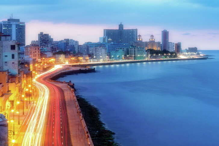 The Malecon seafront promenade at early morning with car light trails on the street, a very calm sea and the skyline of modern Havana with hotels is visible in the background.
