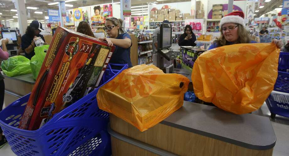 Customer Raquel Diosdado (left) puts a train set into a shopping cart as cashier Jeni Boosey bags other purchases at the Toys R Us at 321 N.W. Loop 410. The National Retail Federation predicted total holiday retail sales could jump 3.6 percent to $655.8 billion from last year's $632.8 billion. Photo: John Davenport /San Antonio Express-News / ©San Antonio Express-News/John Davenport