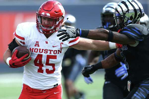 Houston tight end Tyler McCloskey (45) hold off a tackle from Memphis corner back Arthur Maulet (8) as he heads to the end zone for a touchdown in the first half of an NCAA college football game Friday, Nov. 25, 2016, in Memphis, Tenn. (AP Photo/Nikki Boertman)