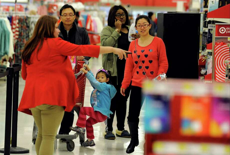 Eric Li pushes a cart while his daughter Iris and wife Leah make there way to check out at the Stamford Target store. Target, in conjuction with Shipt, is launching a same-day delivery service in Stamford on Aug. 14, 2018 and other areas of Connecticut later in the month. Photo: Matthew Brown, Hearst Connecticut Media / Stamford Advocate