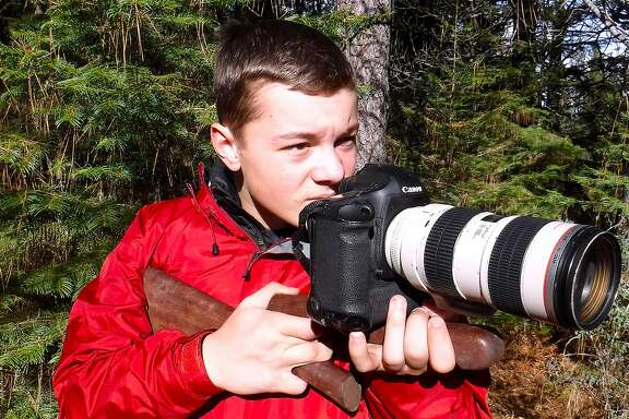 Jack Borden, 15, with a camera mounted on rifle stock, takes part in catch-and-release hunt -- where the participant uses a camera, spotting scope or video camera instead of a firearm, and after a clean shot, the animal walks away unharmed into forest unharmed.