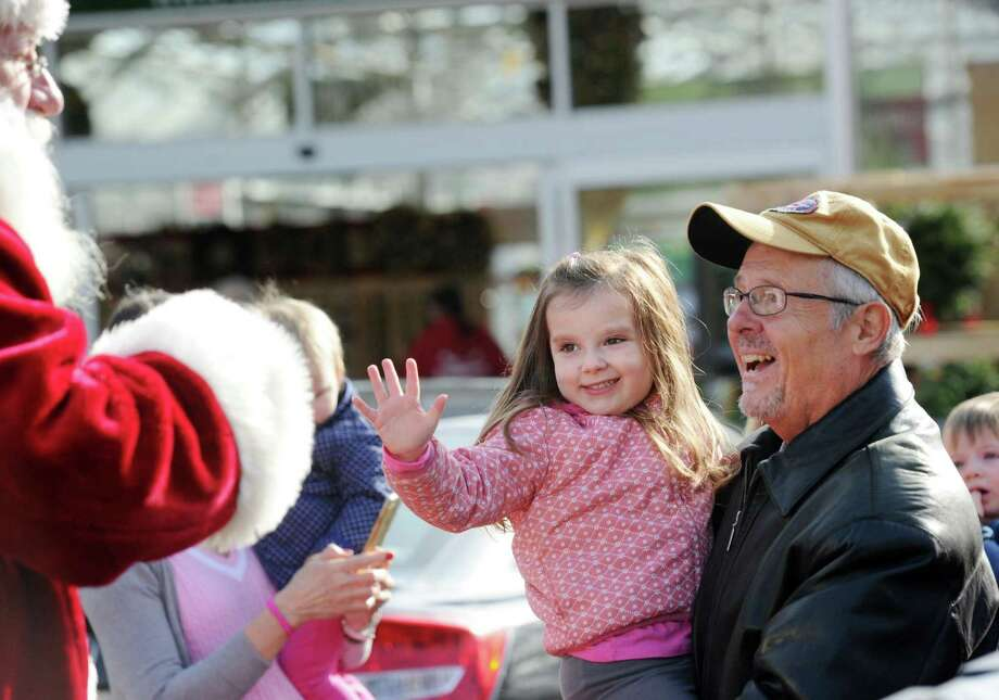 David Bolea holds his granddaughter, Clarissa Maldinado, 4, of Greenwich, who waves to Santa during the 8th annual Greenwich Reindeer Festival & Santa's Village event at Sam Bridge Nursery & Greenhouses at 437 North Street in Greenwich, Conn., Friday, Nov. 25, 2016. The event has photo sessions with Santa, live Reindeer and a carousel ride for children. The event runs through December 24th. See the Sam Bridge Nursery website for the festival's schedule: http://sambridge.com. Photo: Bob Luckey Jr. / Hearst Connecticut Media / Greenwich Time