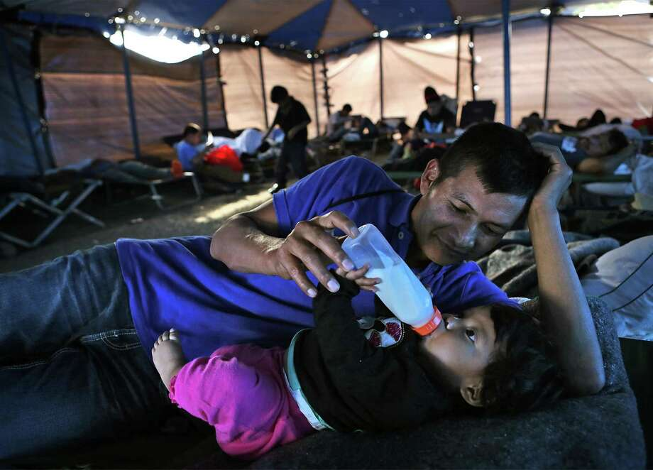 Fernando Pedro Luis Jesus, 31, of Guatemala, feeds his 7 month old daughter Juana Maribel Luis Mateo in a tent shelter at Catholic Charities of the Rio Grande Valley which offers services to immigrants at  Sacred Heart Catholic Church in McAllen, TX, on Tuesday Nov. 22, 2016. Photo: Bob Owen, Staff / San Antonio Express-News / ©2016 San Antonio Express-News