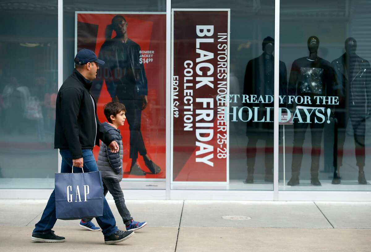 Shoppers walk past Black Friday window displays at the Bay Street shopping district in Emeryville, Calif. on Friday, Nov. 25, 2016.