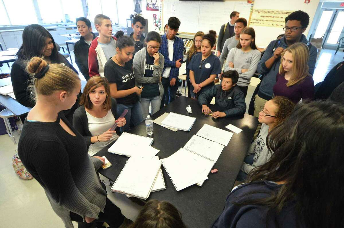 Teacher Sarah Ritz Swain goes from table to table to see to how students are creating a color wheel in their journals during her Art 1 class on Monday November 7, 2016 at Brien McMahon High School in Norwalk Conn.