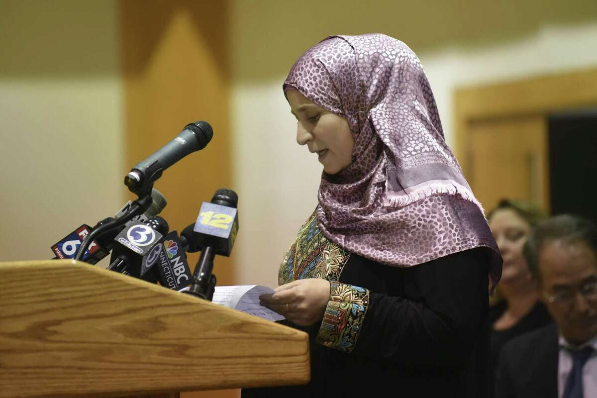 Abeer, a refugee from Syria, talks about her experience during a refugee celebration event that Connecticut Gov. Dannel P. Malloy attended at the Jewish Community Center of Greater New Haven, Tuesday, Nov. 22, 2016, in Woodbridge, Conn. Malloy said Tuesday that he'll sue if the Trump Administration tries to withhold federal funds to New Haven and other so-called sanctuary cities that refuse to cooperate with federal immigration officials. (Jon Olson/Hartford Courant via AP)