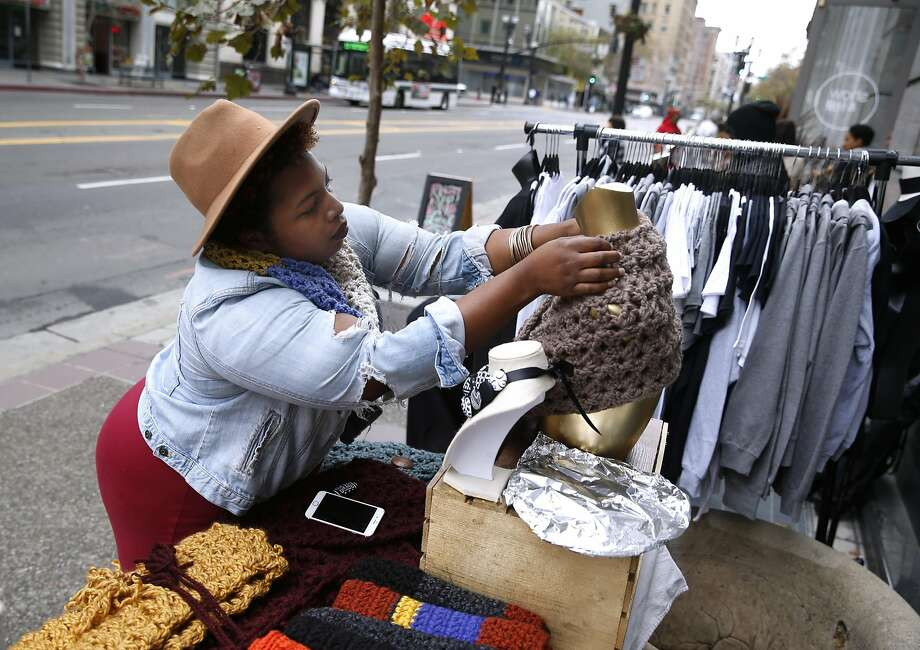 Claudia Patterson arranges a display of her designs at a pop-up stand on Broadway for Plaid Friday sales. Photo: Paul Chinn, The Chronicle