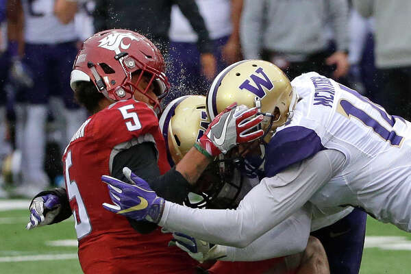 Rain water comes off the helmet of Washington State wide receiver Isaiah Johnson-Mack, left, as he is hit by Washington defensive back Jojo McIntosh, right, and linebacker DJ Beavers, center, on an incomplete pass play in the first half of an NCAA college football game, Friday, Nov. 25, 2016, in Pullman, Wash. (AP Photo/Ted S. Warren)