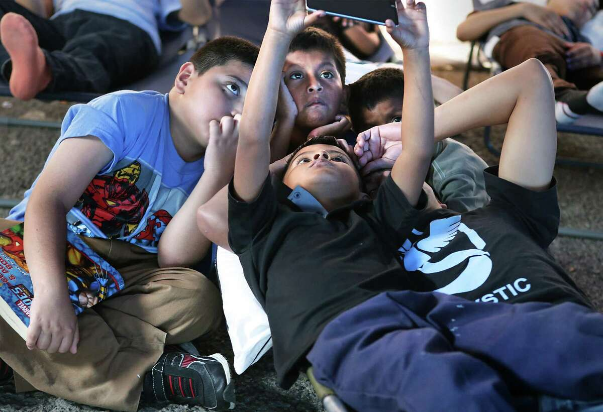 A group of young boys from Central America watch a video on a cell phone in a tent at Sacred Heart Catholic Church while they wait for the departure time of their bus to join family members already in the U.S., on Tuesday Nov. 22, 2016.