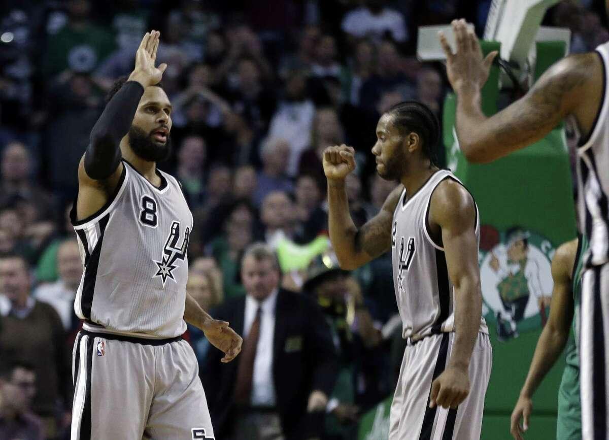 San Antonio Spurs guard Patty Mills (8) celebrates his three-point shot against the Boston Celtics along with Spurs forward Kawhi Leonard, middle, in the fourth quarter of an NBA basketball game, Friday, Nov. 25, 2016, in Boston. The Spurs won 109-103. (AP Photo/Elise Amendola)