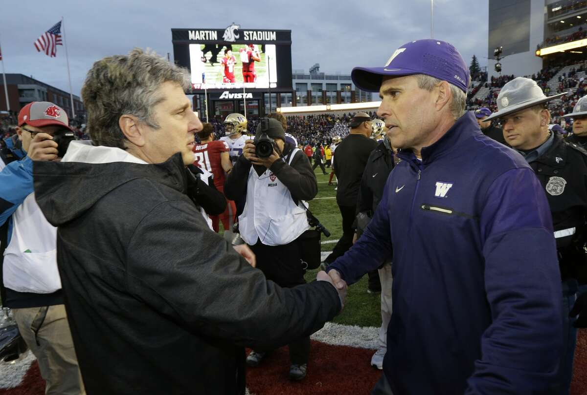 Washington head coach Chris Petersen, right, shakes hands with Washington State head coach Mike Leach, left, after an NCAA college football game, Friday, Nov. 25, 2016, in Pullman, Wash. Washington beat Washington State 45-17. (AP Photo/Ted S. Warren)