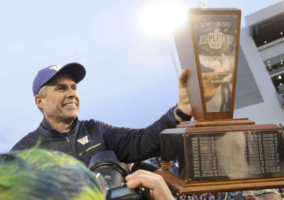 Washington Huskies head coach Chris Petersen hands off the the Apple Cup Trophy after a game against the Washington State Cougars after a game at Martin Stadium. The Huskies won 45-17. Photo: James Snook/USA Today Sports, /via Reuters