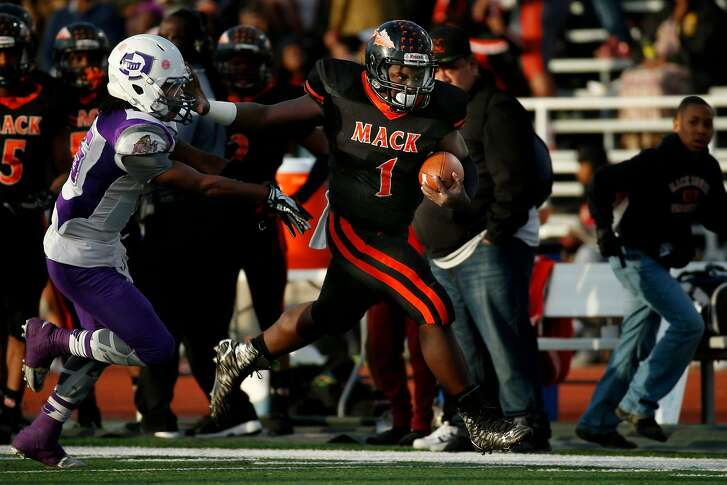 McClymonds Warriors quarterback Emoreea Fountain (1) stiff arms Castlemont Knights cornerback William Perkins (15) for a big gain, during the first half of the Oakland Athletic League Silver Bowl championship football game at Laney College, on Friday, Nov. 25, 2016 in Oakland, Calif.