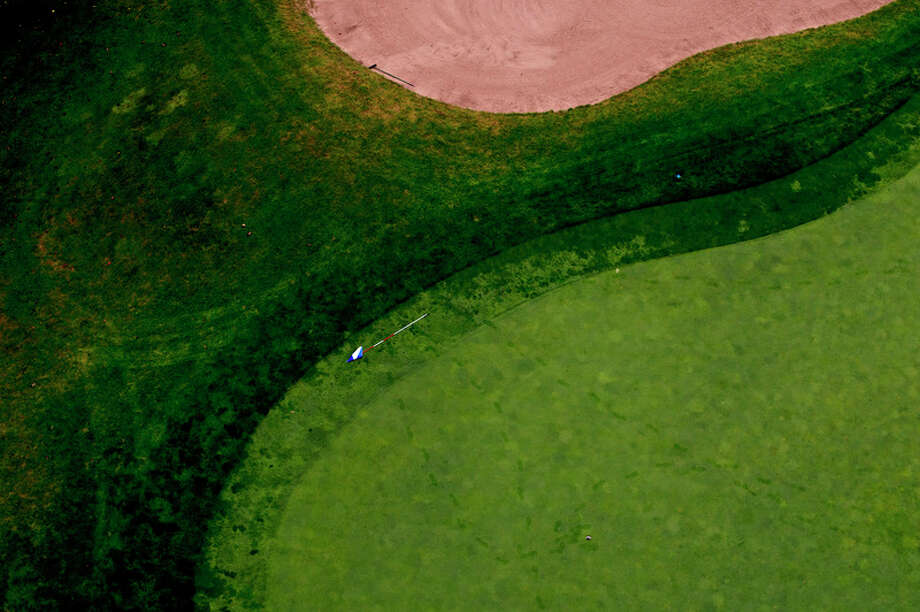 ERIN KIRKLAND | ekirkland@mdn.net  Footprints and a fallen golf course flag at Currie Golf Course are seen during a hot air balloon ride as part of the 2015 Midland Balloon Festival.