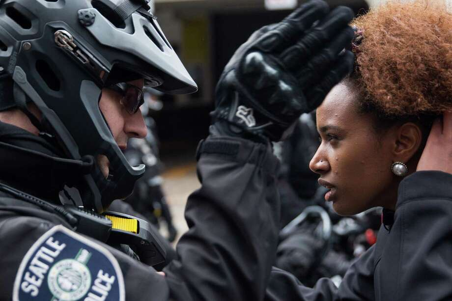 A protester asks a Seattle police officer why they were being stopped at Fourth Avenue and Columbia Street at the annual Black Friday Black Lives Matter protest on Friday, Nov. 25, 2016. Photo: GRANT HINDSLEY, SEATTLEPI.COM / SEATTLEPI.COM