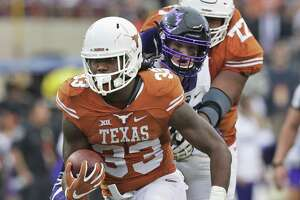 Texas' D'Onta Foreman breaks through an opening untouched and runs for a long gain against TCU at Royal-Memorial Stadium in Austin on Nov. 25, 2016.