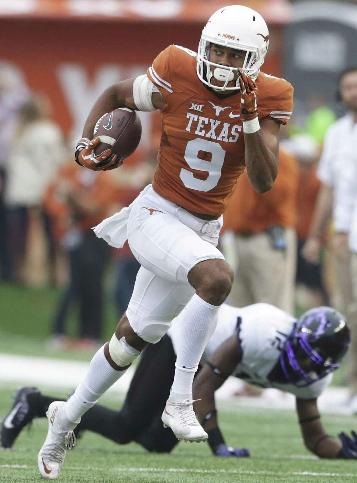 Collin Johnson heads upfield with a catch as Longhorn coach Charlie Strong leads his team against TCU at DKR Stadium on November 25, 2016.