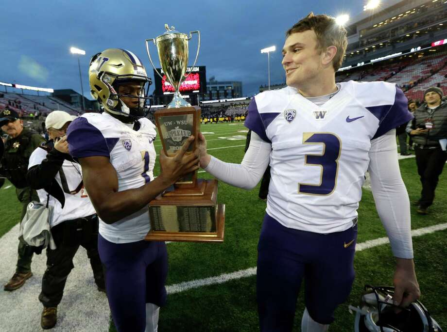 Washington quarterback Jake Browning, right, hands the Apple Cup trophy to receiver John Ross after the Huskies' 45-17 win over state rival Washington State. Photo: Ted S. Warren, STF / Copyright 2016 The Associated Press. All rights reserved.