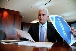 FILE - In this Friday, Nov. 18, 2016, file photo, Energy Transfer Partners CEO Kelcy Warren reviews documents at his office in Dallas on  the Dakota Access oil pipeline that is mired in controversy after thousand of protestors have sought to block its expansion underneath a water source close to the Standing Rock Sioux Indian Reservation in North Dakota. President-elect Donald Trump holds stock in the company building the disputed Dakota Access oil pipeline, and pipeline opponents warn that Trump's investments could undercut any decision he makes on the $3.8 billion project as president. (AP Photo/ John L. Mone, File)