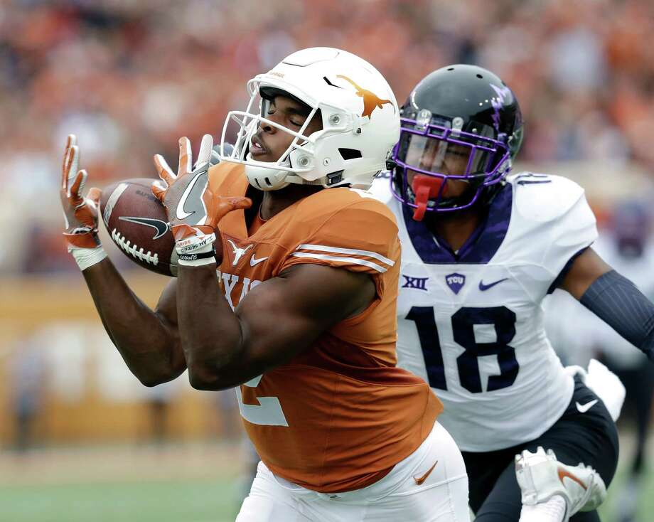 Texas wide receiver Devin Duvernay (2) pulls in a pass in front of TCU safety Nick Orr (18) during the first half of an NCAA college football game, Friday in Austin. Photo: Eric Gay, STF / AP