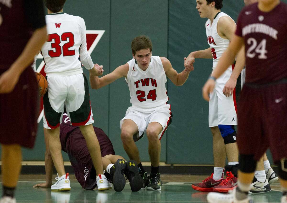 The Woodlands guard Gabe Carbajal (24) is helped up by teammates after taking a charge in the second quarter of a high school boys basketball game during the Guy V. Lewis Invitational at The Woodlands High School Friday, Nov. 25, 2016, in The Woodlands.