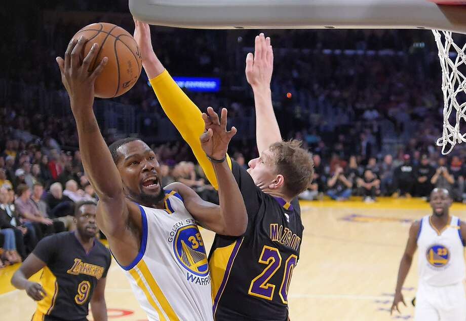 Golden State Warriors forward Kevin Durant, left, shoots as Los Angeles Lakers center Timofey Mozgov, of Russia, defends during the first half of an NBA basketball game, Friday, Nov. 25, 2016, in Los Angeles. Photo: Mark J. Terrill, Associated Press