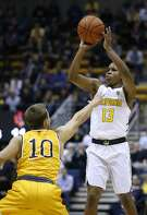 California guard Charlie Moore (13) shoots over Wyoming's Brandon Chauca (10) during the first half of an NCAA college basketball game Friday, Nov. 25, 2016, in Berkeley, Calif. (AP Photo/Tony Avelar)