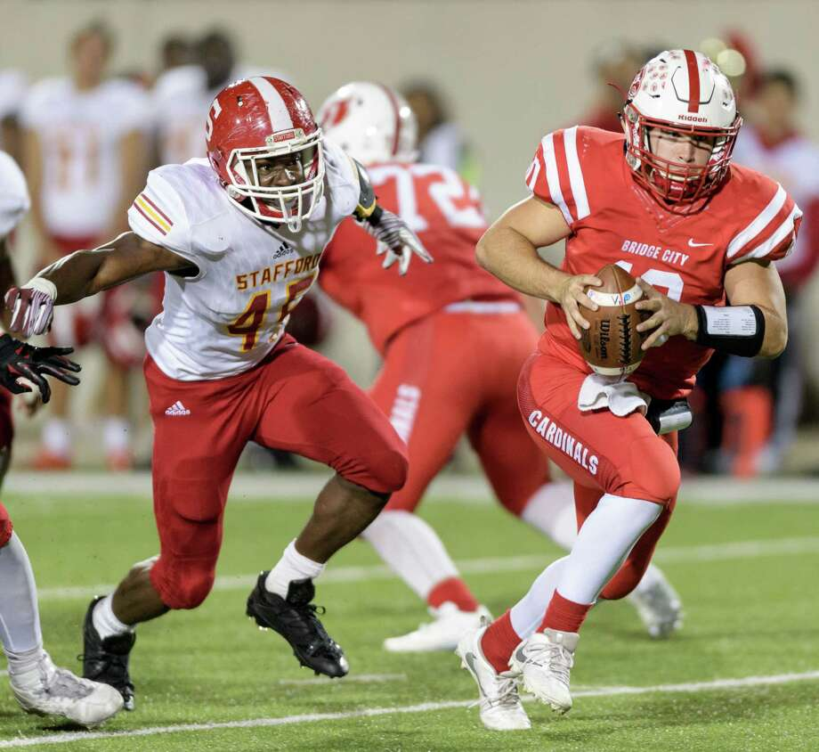 Byron Trahan (10) of the Bridge City Cardinals scrambles from Charles Hester (45) of the Stafford Spartans in the first half in a high school football Class 4A, Division 1 Regional Semifinal on Friday, November 25, 2016 at Maddry Stadium in Channelview Texas. Photo: Wilf Thorne / © 2016 Houston Chronicle
