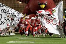 Byron Trahan (10) of the Bridge City Cardinals brings his team on the field against the Stafford Spartans in a high school football Class 4A, Division 1 Regional Semifinal on Friday, November 25, 2016 at Maddry Stadium in Channelview Texas.