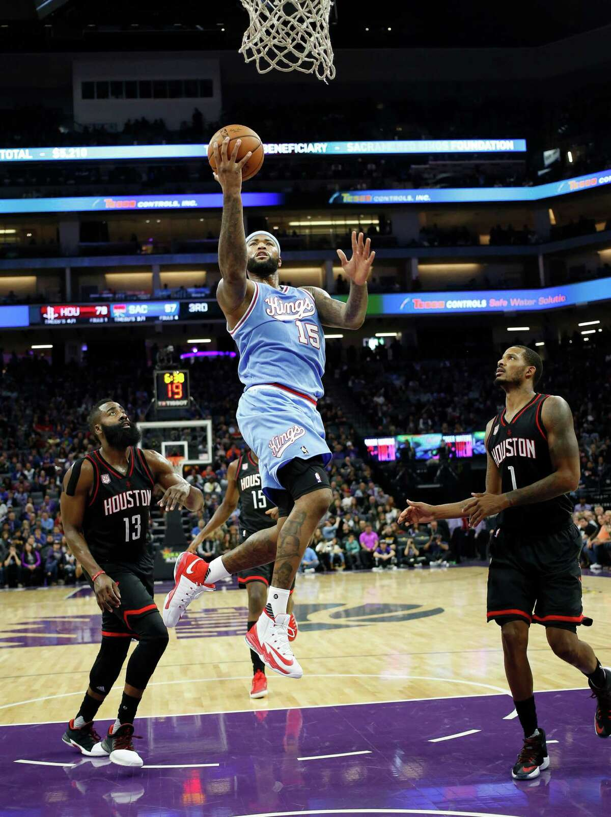 Sacramento Kings center DeMarcus Cousins, center, drives to the basket between Houston Rockets' James Harden, left, and Trevor Ariza during the second half of an NBA basketball game in Sacramento, Calif., Friday, Nov. 25, 2016. The Rockets won 117-104. (AP Photo/Rich Pedroncelli)