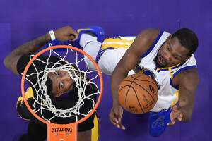 Golden State Warriors forward Kevin Durant, right, shoots as Los Angeles Lakers forward Thomas Robinson defends during the second half of an NBA basketball game, Friday, Nov. 25, 2016, in Los Angeles. The Warriors won 109-85. (AP Photo/Mark J. Terrill)
