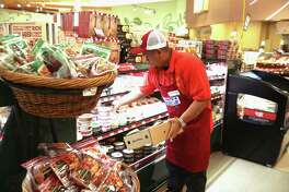 An employee stocks cheese at the Kroger on Buffalo Speedway. ( Dylan Aguilar / Houston Chronicle )